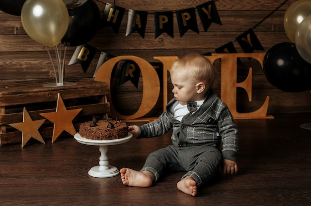 Een kleine jongen in een grijs pak viert zijn eerste verjaardag en breekt een taart op een bruine achtergrond met decor