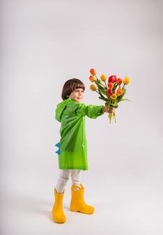 Een kleine jongen in een groene regenjas en gele rubberen laarzen geeft een boeket van kleurrijke tulpen op een witte achtergrond met een plek voor tekst