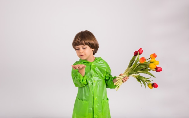 Een kleine jongen in een groene regenjas houdt een boeket kleurrijke tulpen vast en stuurt een luchtkus op een blauwe achtergrond met een plek voor tekst