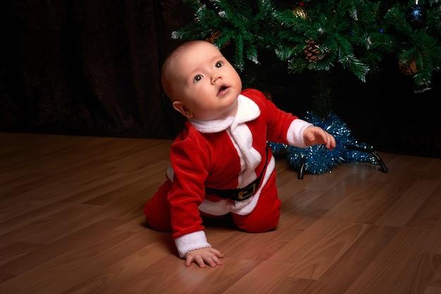 Een kleine jongen in een rood kerstmanpak bij de kerstboom