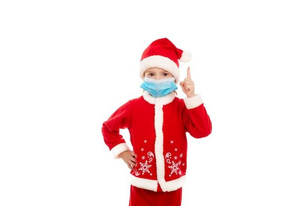 Een kleine jongen in een rood pak van de kerstman in een medisch masker steekt zijn wijsvinger op