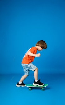 Een kleine jongen in een t-shirt en korte broek rijdt op een skateboard op een blauwe ondergrond met ruimte voor tekst