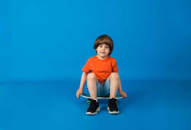 Een kleine jongen in een t-shirt en korte broek zit op een skateboard op een blauwe ondergrond met ruimte voor tekst