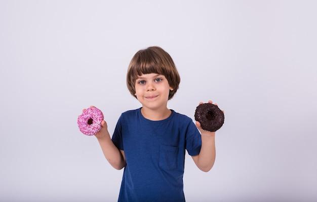 Een kleine jongen in een t-shirt houdt donuts vast op een witte achtergrond met een kopie van de spatie