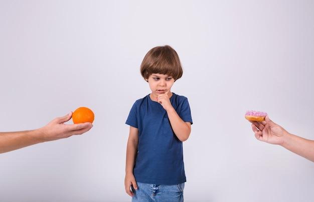 Een kleine jongen in een t-shirt maakt een keuze tussen een sinaasappel en een donut op een witte achtergrond met een plek voor tekst