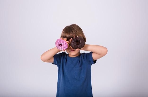 Een kleine jongen in een t-shirt sloot zijn ogen twee donuts op een witte achtergrond met een plek voor tekst