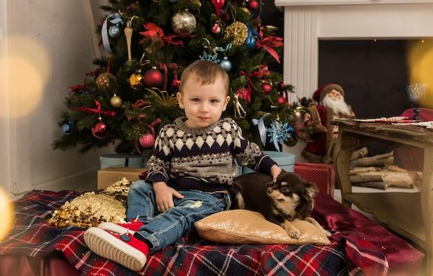 Een kleine jongen in een trui zit met een hond op de achtergrond van een kerstboom