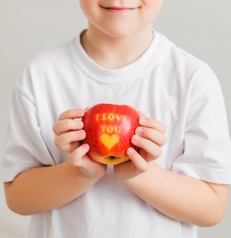 Een kleine jongen in een wit t-shirt heeft een appel in zijn handen met het opschrift i love you. verticale foto