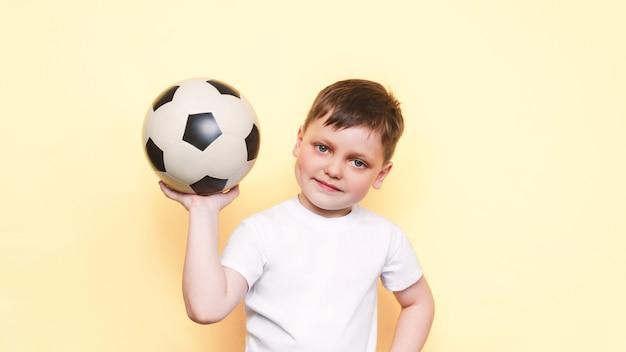 Een kleine jongen in een wit t-shirt met een voetbal in zijn hand glimlacht geïsoleerd op beige achtergrond