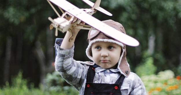 Een kleine jongen in helmvliegerpiloot van een vliegtuig speelt met een houten vliegtuig het kind droomt van vliegen