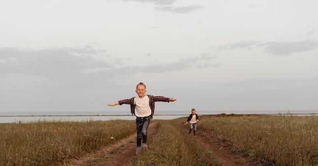 Een kleine jongen in jeanskleren rent met uitgestrekte armen naar de kijker over het veld.