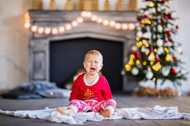 Een kleine jongen in kerstpyjama die huilt tegen de achtergrond van een boom en een open haard. hoge kwaliteit foto