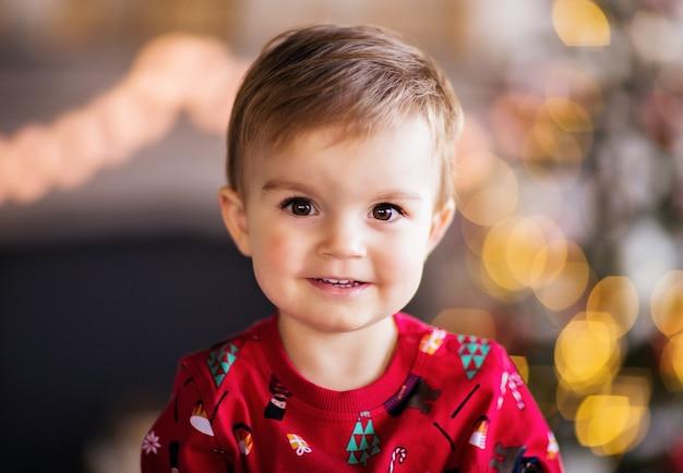 Een kleine jongen in kerstpyjama lacht tegen de achtergrond van een boom en een open haard. hoge kwaliteit foto