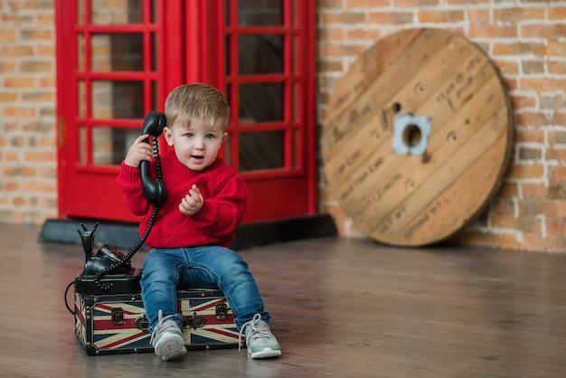 Een kleine jongen is aan het telefoneren bij een rode engelse telefooncel
