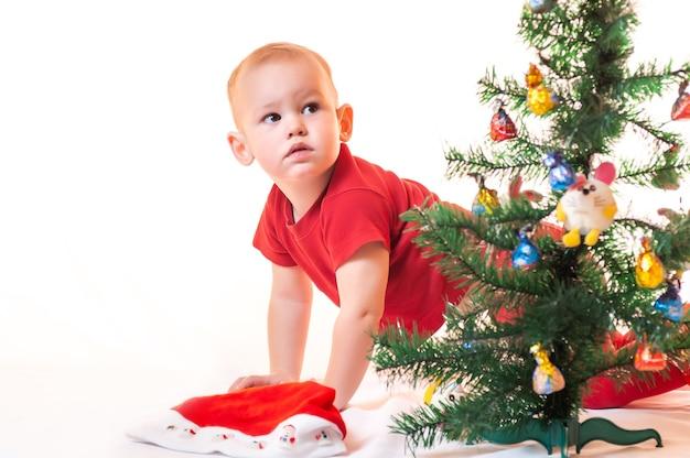 Een kleine jongen is op zoek naar cadeaus van de kerstman onder de kerstboom.