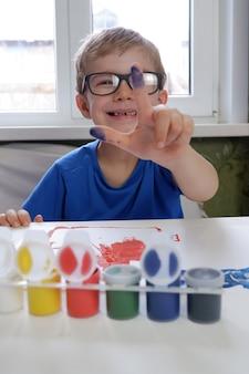 Een kleine jongen laat zijn vingers in de verf zien. creativiteit van kinderen thuis.