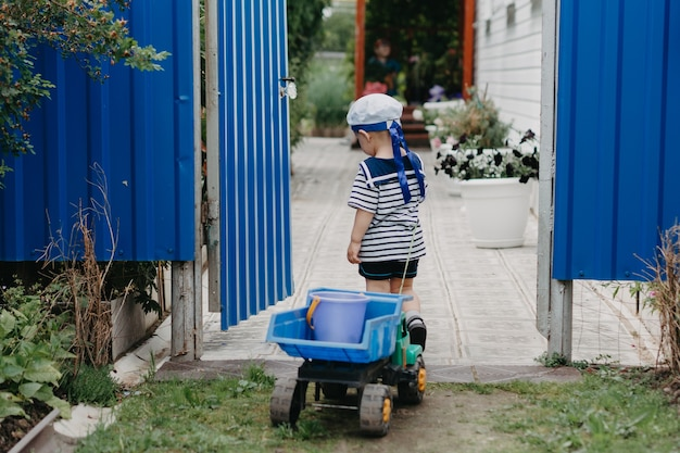 Een kleine jongen lacht en rijdt buiten in een speelgoedautootje aan een touwtje