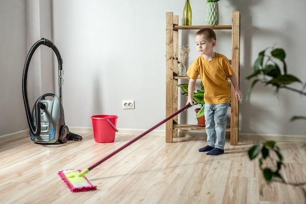 Een kleine jongen maakt de vloer van een kamer schoon met een dweil. concept van onafhankelijkheid, hulp aan ouders, huishoudelijk werk van het kind