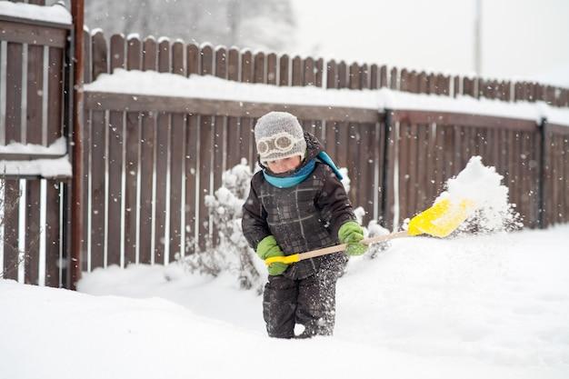 Een kleine jongen maakt schoppaden in de tuin van sneeuw schoon