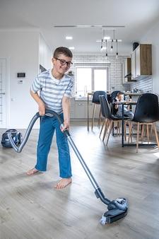 Een kleine jongen met bril maakt het huis schoon met een stofzuiger.