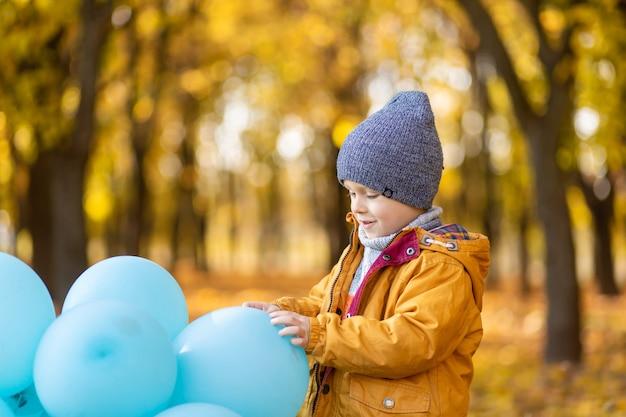 Een kleine jongen met een armvol ballonnen loopt in het herfstpark. gele bomen en blauwe ballen. stijlvol kind.
