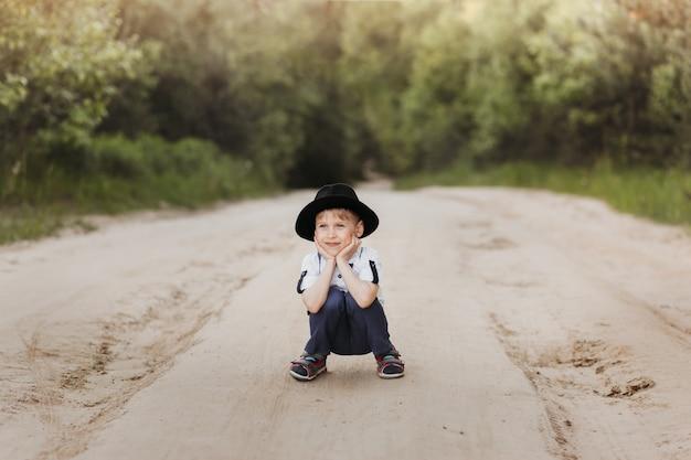 Een kleine jongen met een hoed loopt in de zomer op een zonnige dag in de natuur. natuur op het land