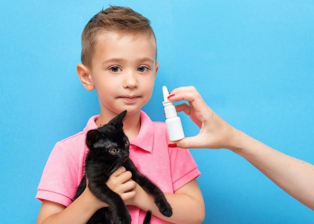 Een kleine jongen met een kitten in zijn armen en zijn moeders hand met anti-allergische neusspray op blauw