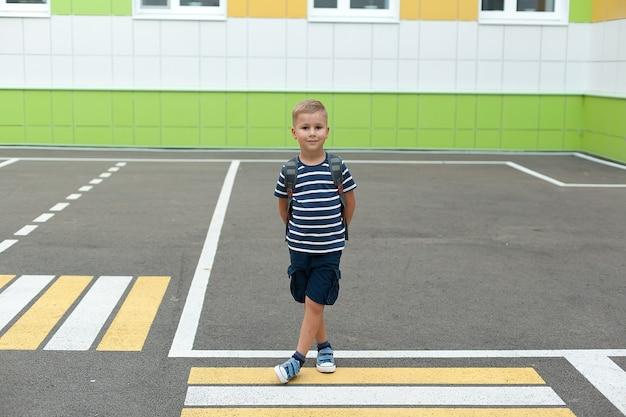 Een kleine jongen met een rugzak, die in zijn eentje de weg overstak bij de school