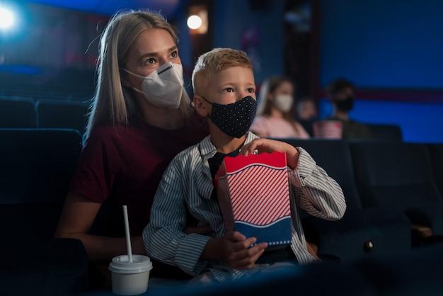 Een kleine jongen met moeder die popcorn eet in de bioscoop, films kijkt en het coronavirusconcept.