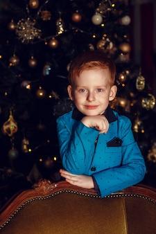Een kleine jongen met rood haar en sproeten op een donkere achtergrond. goud en zwart. kerstboom en nieuwjaarsversieringen