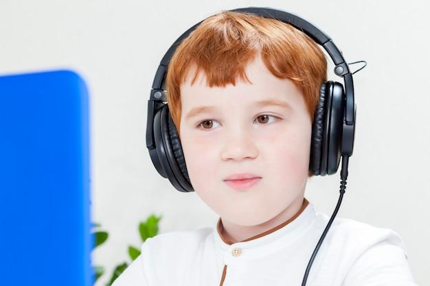 Een kleine jongen met rood haar, luisteren naar muziek via een koptelefoon op het hoofd dragen