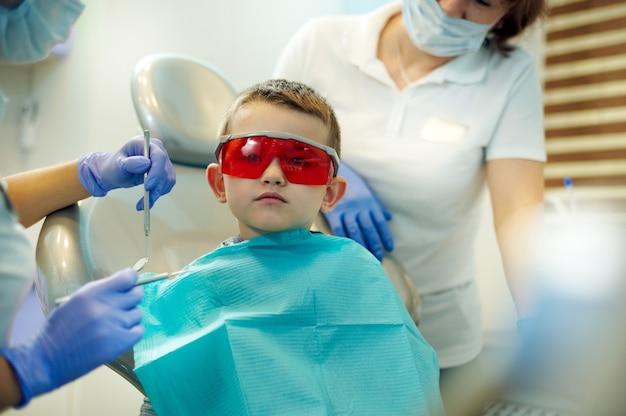 Een kleine jongen op een tandartsstoel tijdens bezoek aan tandarts