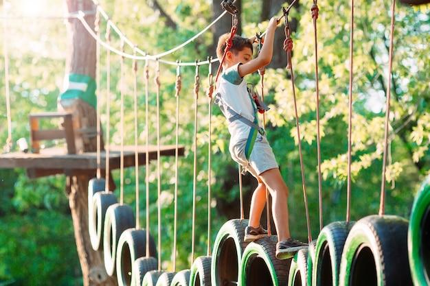 Een kleine jongen passeert het obstakel in het touwpark