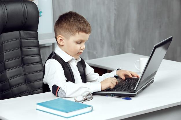 Een kleine jongen portretteert de baas op kantoor, zittend in een stoel en werkend op een laptop