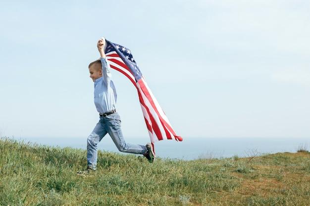 Een kleine jongen rent met de vlag van de verenigde staten. 4 juli onafhankelijkheidsdag.