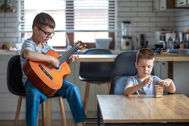Een kleine jongen speelt gitaar en zijn broer bouwt thuis aan tafel een torentje met houten kubussen.
