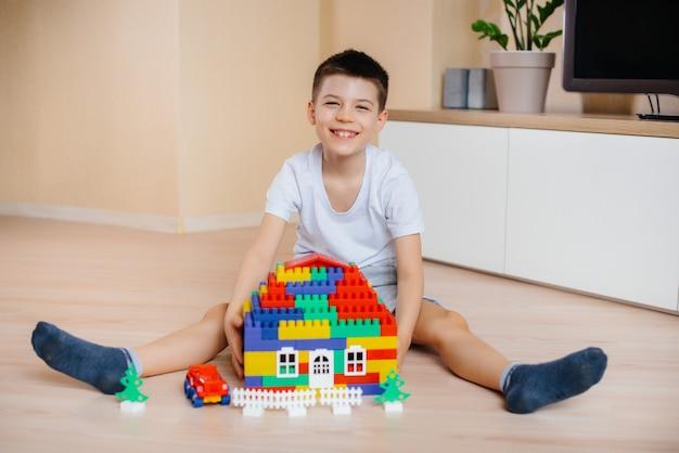 Een kleine jongen speelt met een bouwpakket en bouwt een groot huis voor het hele gezin. bouw van een gezinswoning.