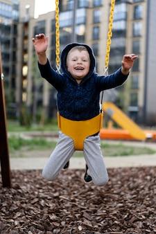 Een kleine jongen speelt plezier op de moderne stedelijke europese speelplaats