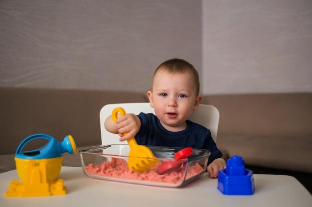 Een kleine jongen speelt thuis met zand. kinetische zand- en zandbakset. spelletjes voor sensorische ontwikkeling van kinderen.