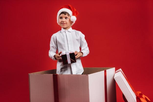 Een kleine jongen staat in een geschenkdoos met een kerstcadeau in zijn handen