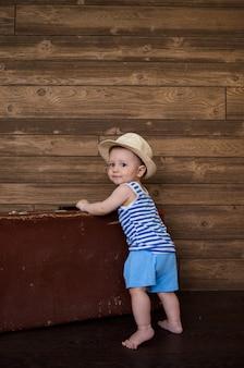 Een kleine jongen staat naast een retro koffer op een bruine houten ondergrond met ruimte voor tekst