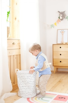Een kleine jongen stopt speelgoed in een scandinavische mand voor een kinderkamer. eco-vriendelijke inrichting kinderkamer. portret van een jongen die in kleuterschool speelt. kinderkamer en interieurontwerp. babyjongen thuis.