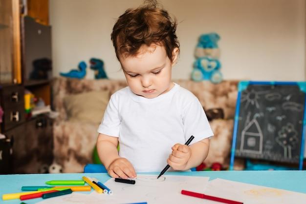 Een kleine jongen tekent met kleurpotloden op vellen papier die op tafel liggen