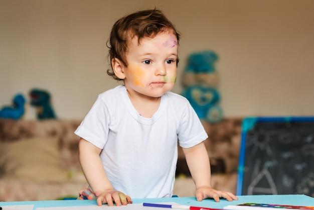 Een kleine jongen tekent met kleurrijke stiften op een vel papier