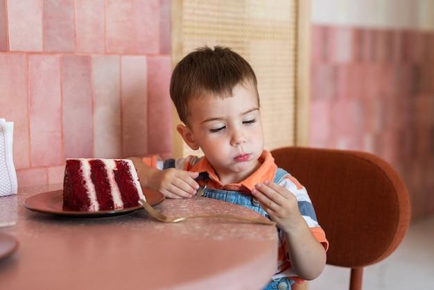 Een kleine jongen van 23 jaar zit in een café en eet een taart op een schotel ligt een groot stuk taart