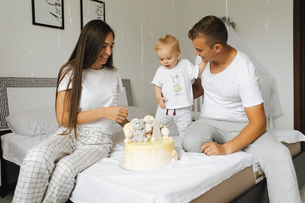 Een kleine jongen verheugt zich over de verjaardagstaart van zijn ouders