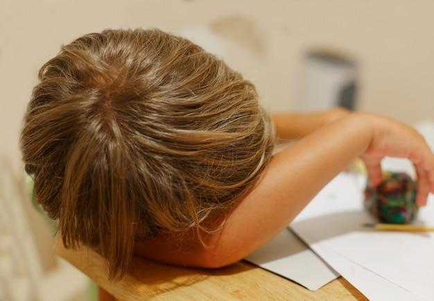 Een kleine jongen viel tijdens het spelen aan tafel in slaap