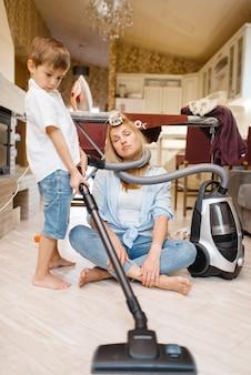 Een kleine jongen wikkelde de huisvrouw met een slang van de stofzuiger. vrouw doet huishoudelijk werk thuis. vrouwelijke persoon met haar speelse zoon die in huis aan het dollen is