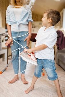 Een kleine jongen wikkelde een huisvrouw met draden. vrouw doet huishoudelijk werk thuis. vrouwelijke persoon met haar speelse zoon die in huis aan het dollen is