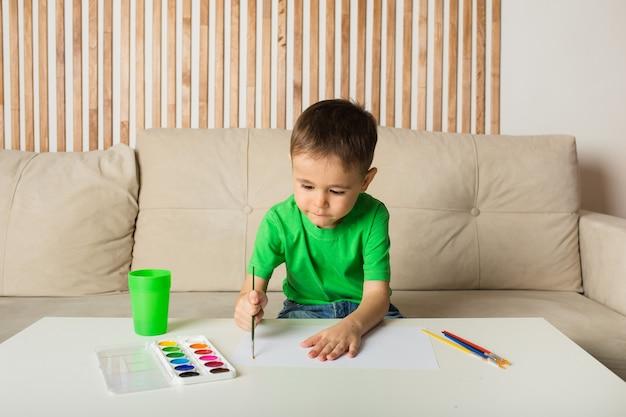 Een kleine jongen zit aan een tafel en tekent met een penseel en schildert op wit papier in een kamer